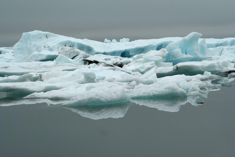 Reflexões dos icerbergs azuis e brancos de cristal na água escura preta na luz sombrio não ofuscante imagens de stock
