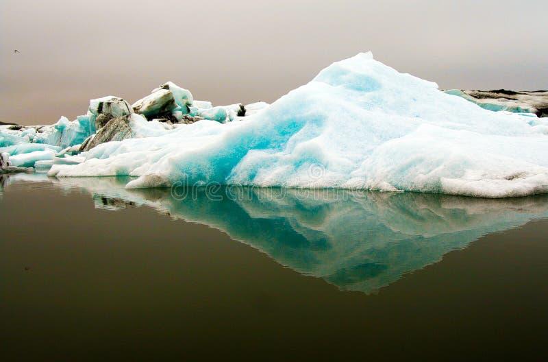 Reflexões dos icerbergs azuis e brancos de cristal na água escura preta na luz sombrio não ofuscante fotografia de stock