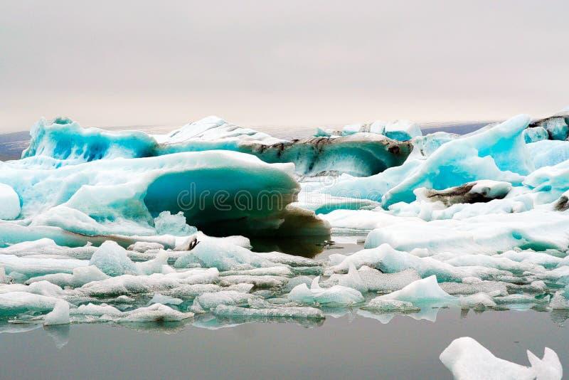 Reflexões dos icerbergs azuis e brancos de cristal na água escura preta na luz sombrio não ofuscante imagem de stock