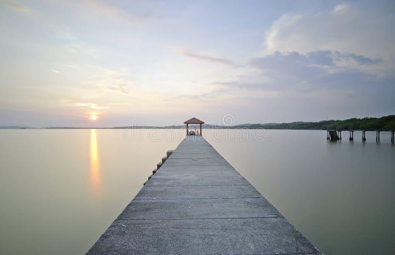 Reflexões magníficas do por do sol e do lago no molhe longo fotografia de stock