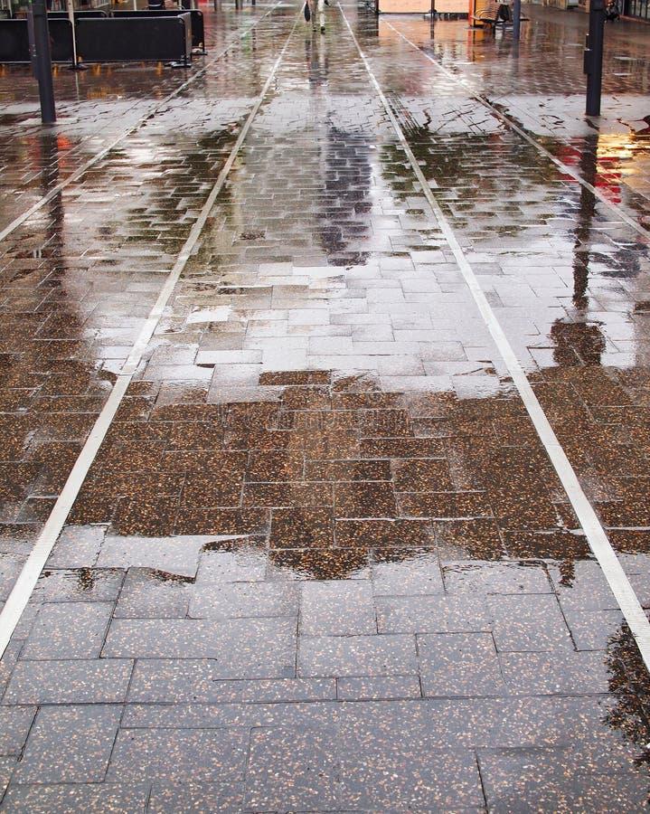 Reflexões na alameda pedestre pavimentada molhada fotografia de stock