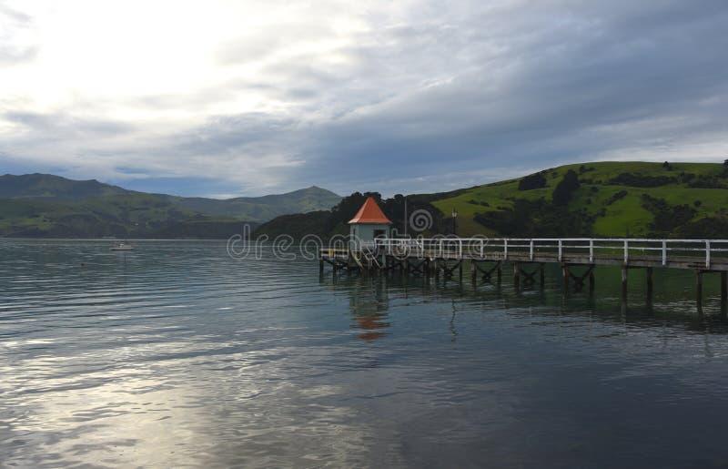 Reflexões novas do céu do por do sol de Zealand Akaroa- imagens de stock