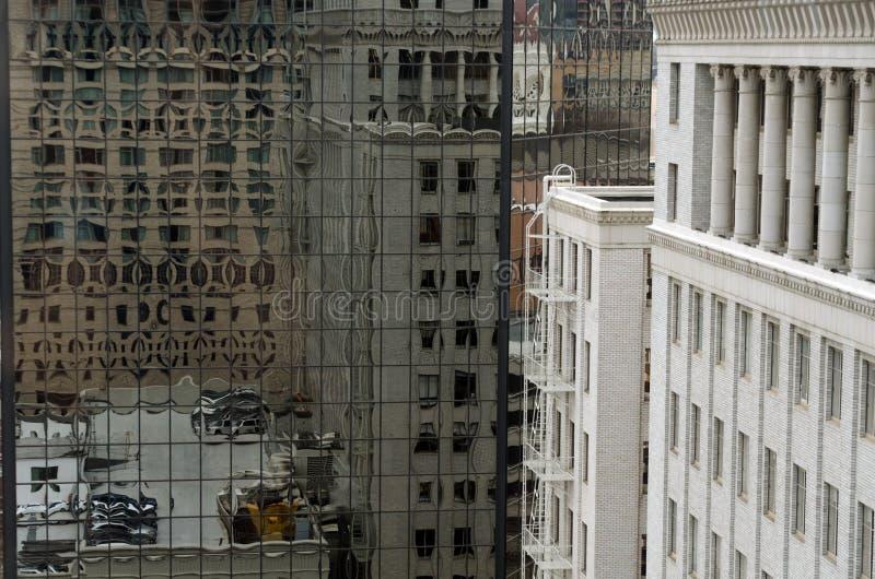 Reflexões sobre assentos e telhados na parede de vidro de um arranha-céu na Sexta Avenida imagem de stock