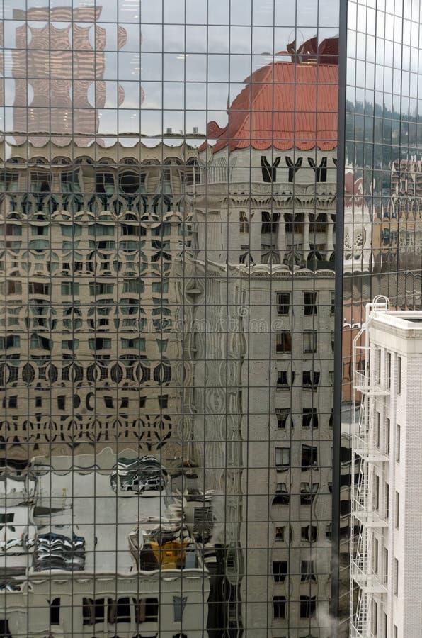 Reflexões sobre assentos e telhados na parede de vidro de um arranha-céu na Sexta Avenida fotografia de stock