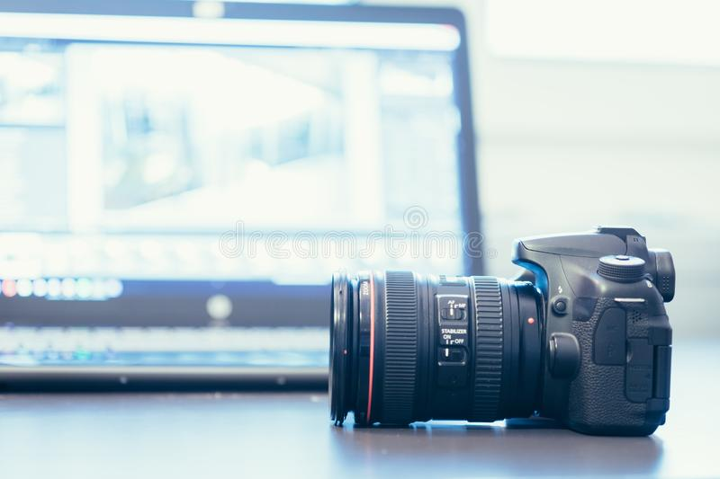 Reflex camera with professional telephoto lens on a table, laptop in the blurry background. Professional camera with telephoto lens on a table, laptop in the royalty free stock images
