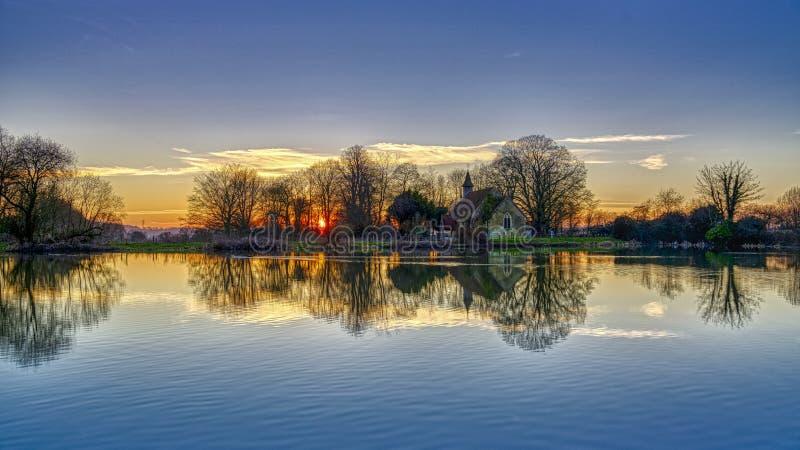 Reflex?es da igreja de St Leonard em Hartley Mauditt Pond, penas sul parque nacional, Reino Unido fotografia de stock royalty free