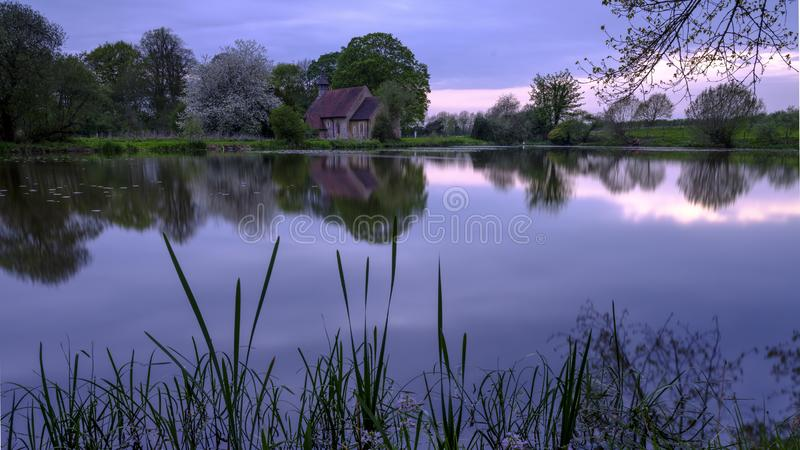 Reflex?es da igreja de St Leonard em Hartley Mauditt Pond, penas sul parque nacional, Reino Unido foto de stock