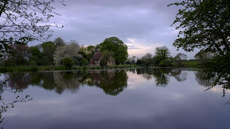 Reflex?es da igreja de St Leonard em Hartley Mauditt Pond, penas sul parque nacional, Reino Unido fotos de stock
