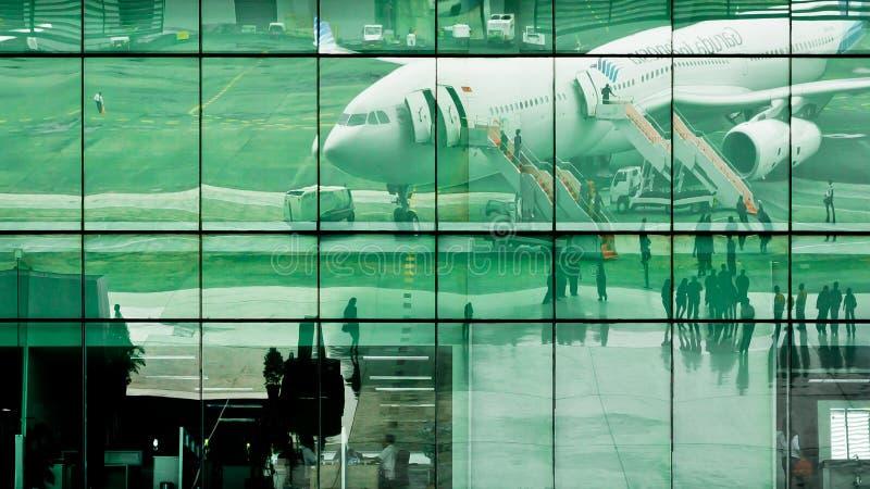 Reflex?o de espelho de uma entrada da casa da quinta Atividade de aeroporto de Soekarno Hatta no parque de estacionamento dos avi imagens de stock royalty free