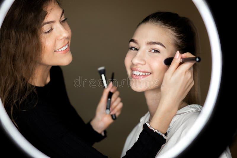 A reflex?o no espelho do maquilhador a menina encantador est? fazendo a composi??o a uma mo?a bonita foto de stock royalty free