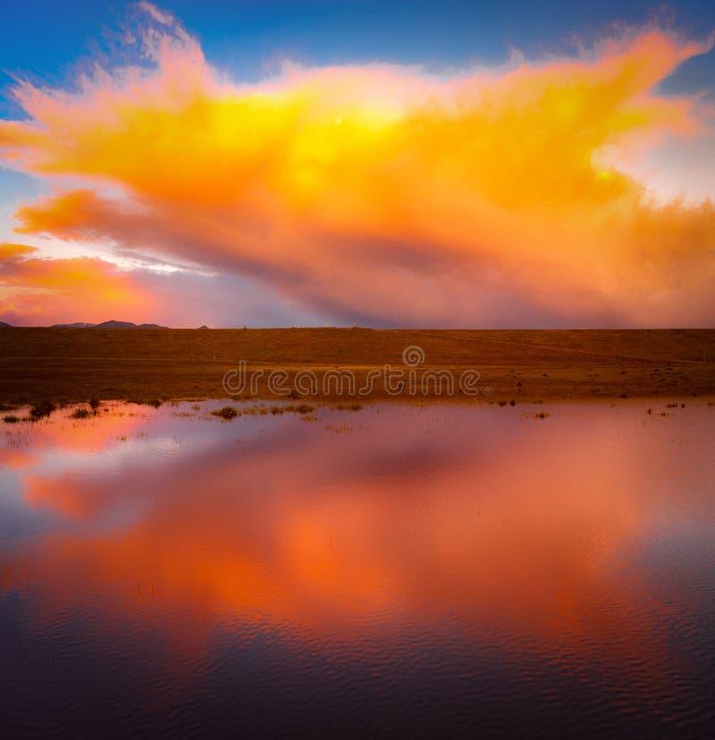 Reflexión anaranjada de la nube sobre un lago imagen de archivo