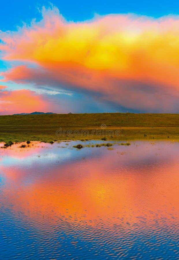 Reflexión anaranjada de la nube sobre un lago fotografía de archivo