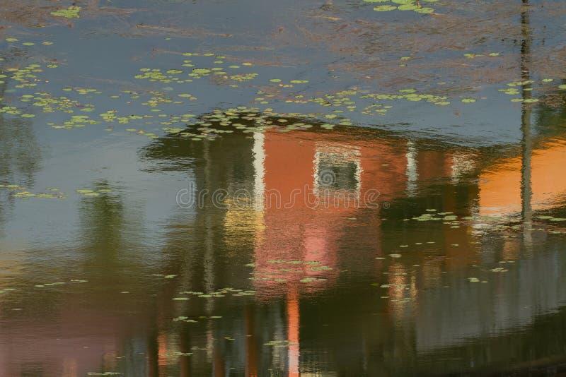 Reflexión de casas en el agua Superficie de una charca de la ciudad imagenes de archivo