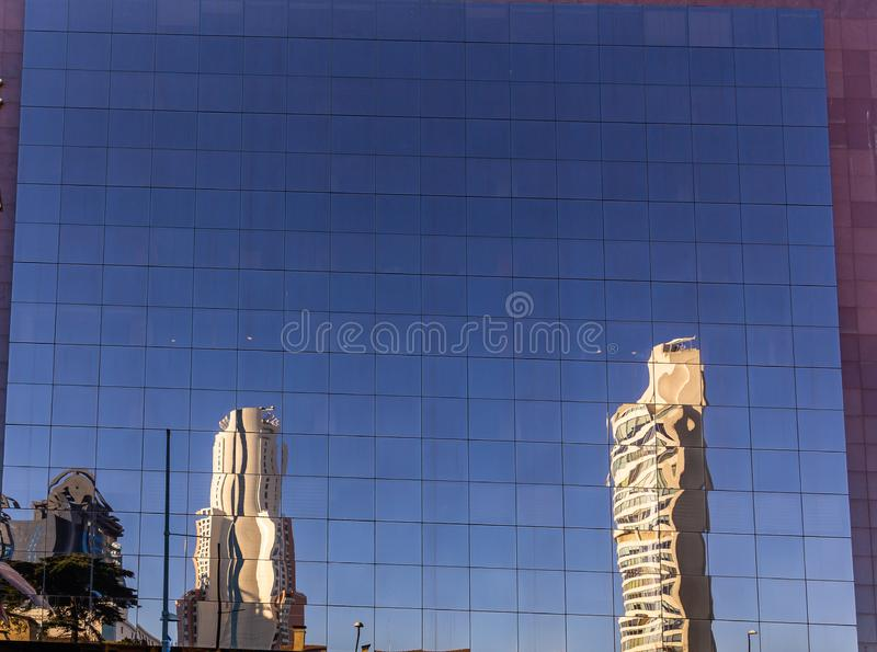 Reflexión de edificios altos y del cielo azul brillante en una fachada de cristal en Estambul, Turquía foto de archivo libre de regalías