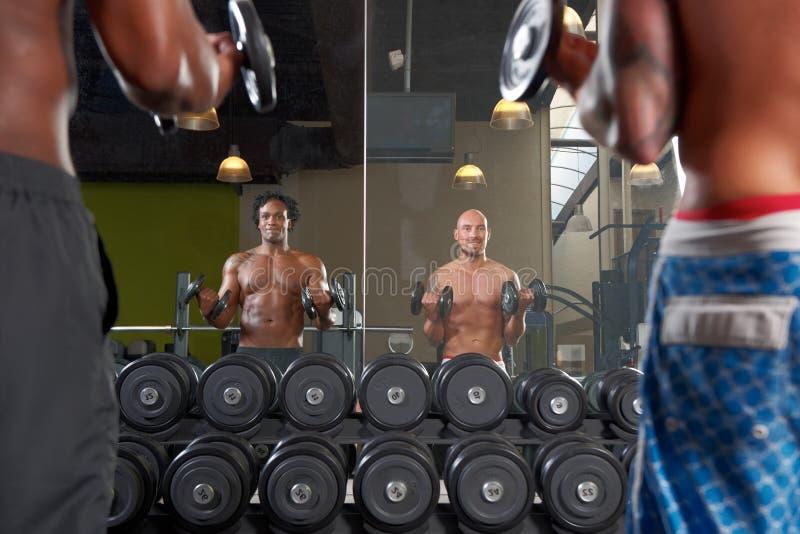 Reflexión de espejo de dos hombres que ejercitan en gimnasio fotografía de archivo libre de regalías