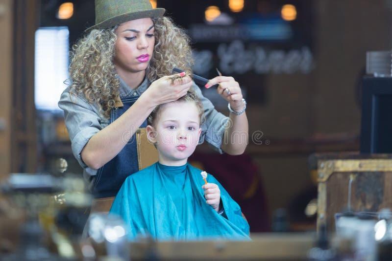 Reflexión de espejo del pelo del muchacho del corte de la mujer joven foto de archivo libre de regalías