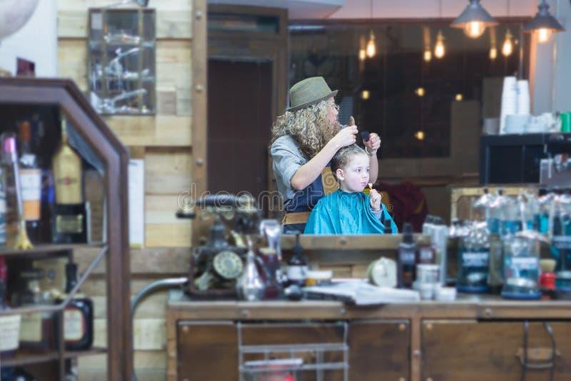 Reflexión de espejo del peluquero y del muchacho fotografía de archivo