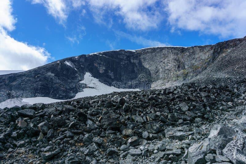 Reflexión de la cadena de montaña en un pequeño lago en el parque nacional de Jotunheimen en Noruega imagen de archivo