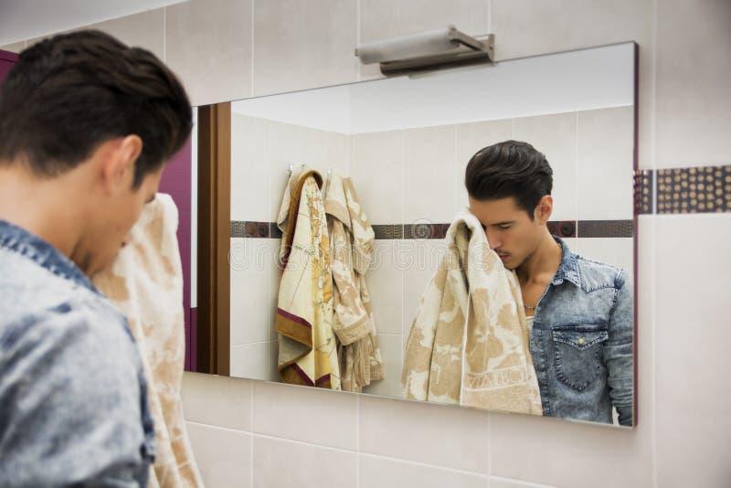 Reflexión de la cara de sequía del hombre con la toalla en espejo fotos de archivo libres de regalías