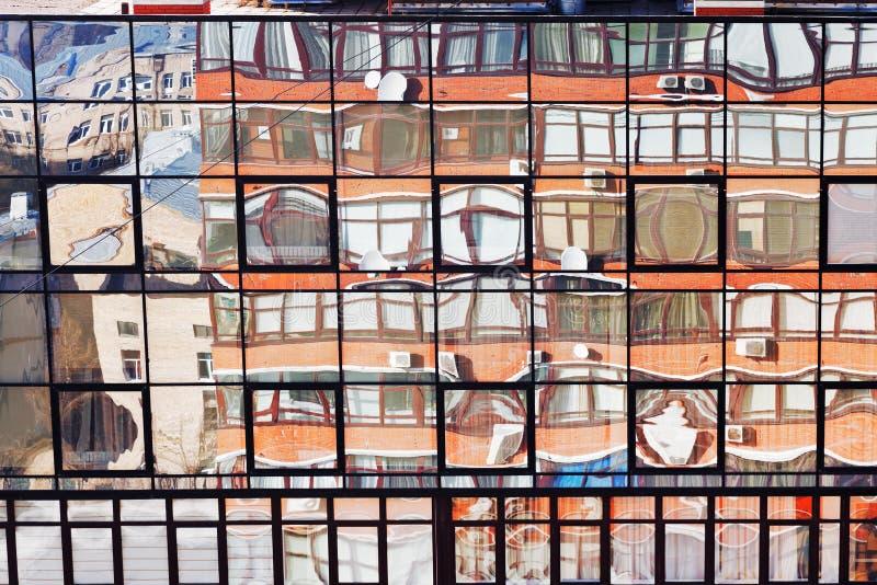 Reflexión de la casa del ladrillo en la pared de cristal fotografía de archivo
