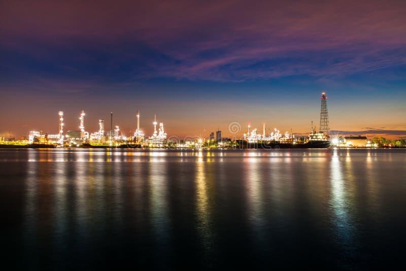 Reflexión de la industria de la refinería de petróleo en el agua en la madrugada debajo del cielo colorido de la salida del sol imagen de archivo