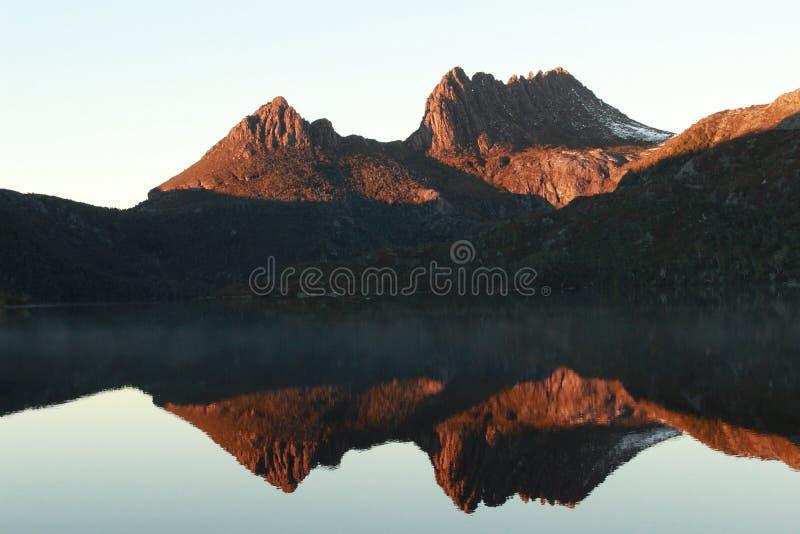 Reflexión de la montaña de la cuna en la salida del sol imágenes de archivo libres de regalías