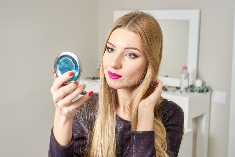 Reflexión de la mujer hermosa joven que aplica su maquillaje, mirando en un espejo foto de archivo