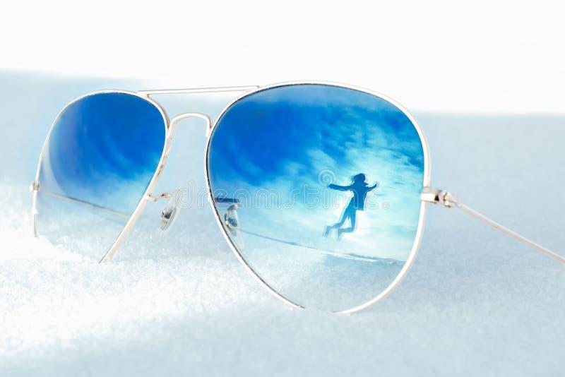 Reflexión de la mujer de salto feliz en un paisaje del invierno con efecto partido Gafas de sol en nieve Libertad y alegría del c foto de archivo libre de regalías
