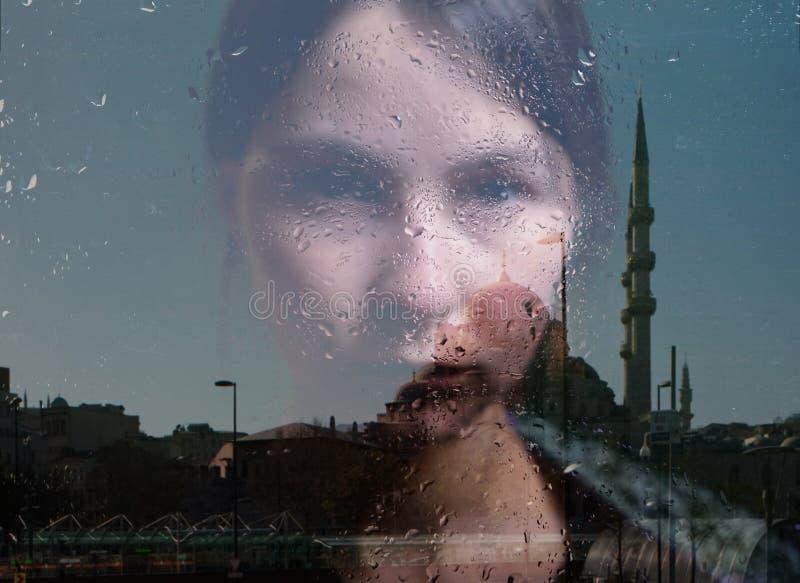 Reflexión de la mujer y de la mezquita en la ventana foto de archivo libre de regalías