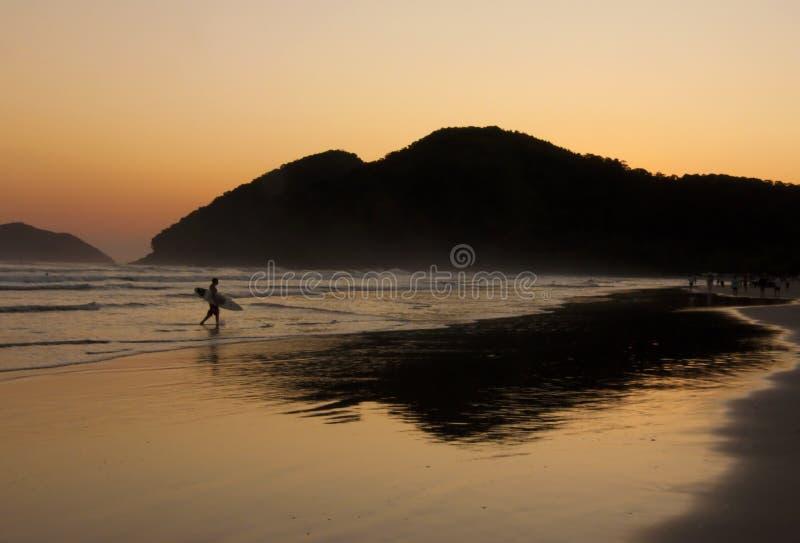 Reflexión de la persona que practica surf y de la puesta del sol en una playa tropical imagenes de archivo