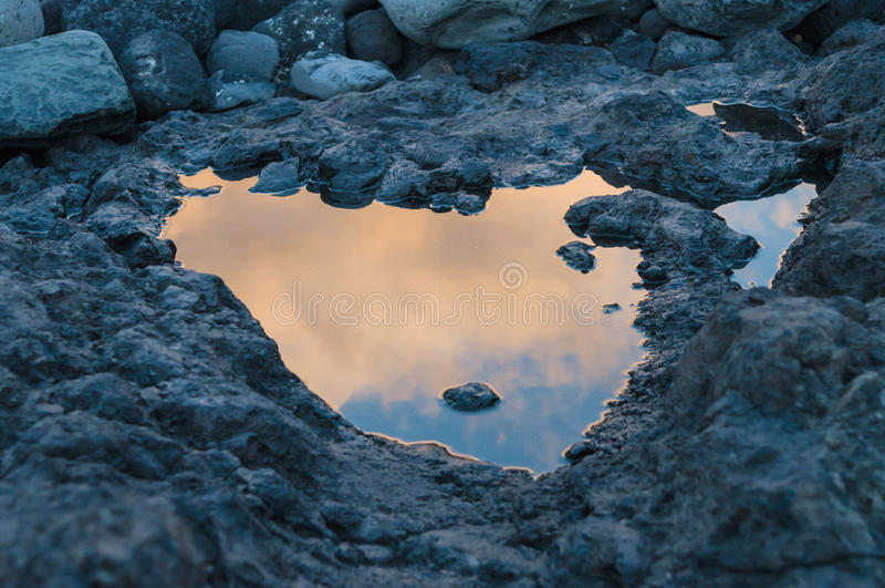 Reflexión de la puesta del sol en pequeño charco en la tierra volcánica fotos de archivo libres de regalías