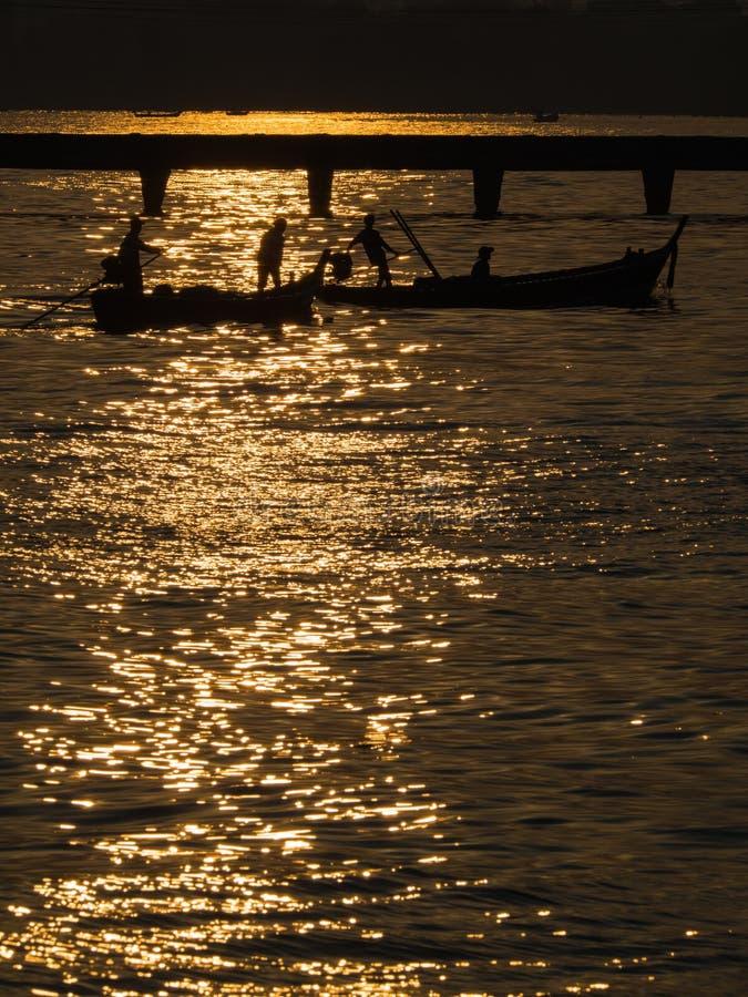 Reflexión de la salida del sol al mar, a los barcos y al puente imagen de archivo libre de regalías