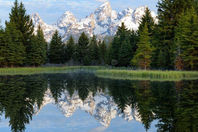 Reflexión de la salida del sol de las montañas coronadas de nieve fotos de archivo