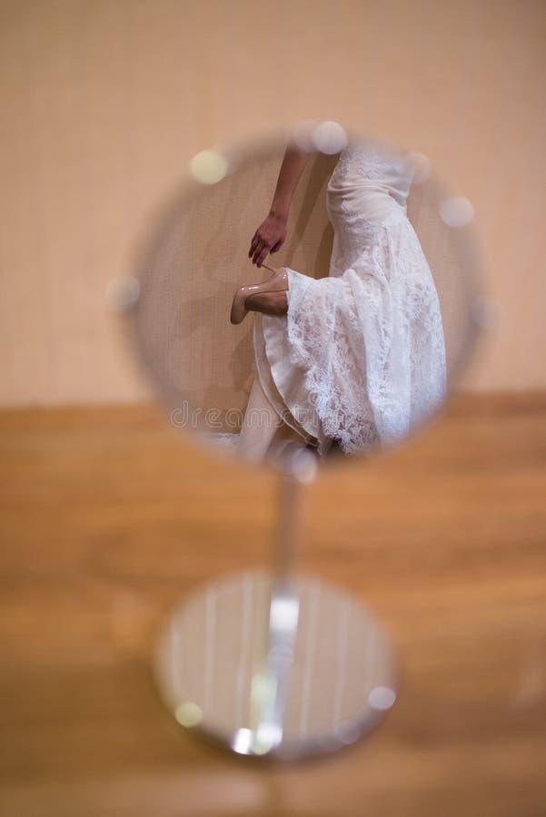Reflexión de los zapatos beige del ` s de la novia en el espejo indoor imágenes de archivo libres de regalías
