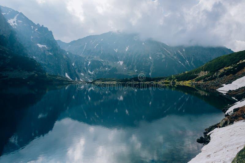 Reflexión de montañas en el agua del cielo de la charca de Czarny Staw, montañas de Tatra, Polonia foto de archivo libre de regalías
