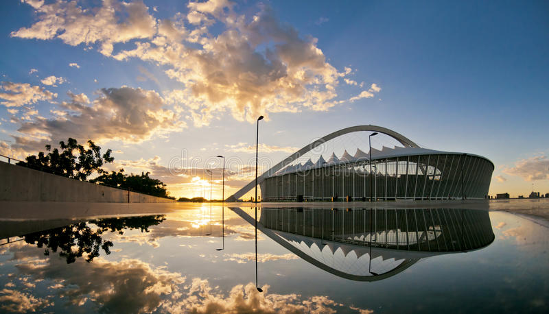 Reflexión de Moses Mabhida Stadium en la salida del sol imagenes de archivo