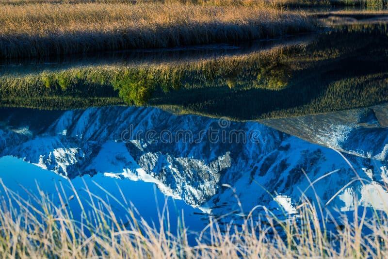 Reflexión de picos de rocas en el espejo fotos de archivo