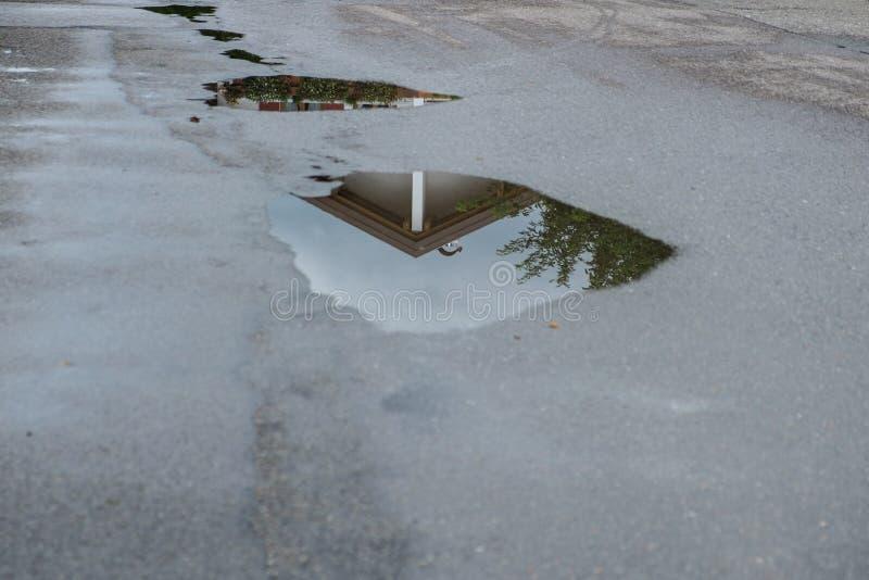 Reflexión de una casa en un charco del agua después de una tormenta de la lluvia imagen de archivo