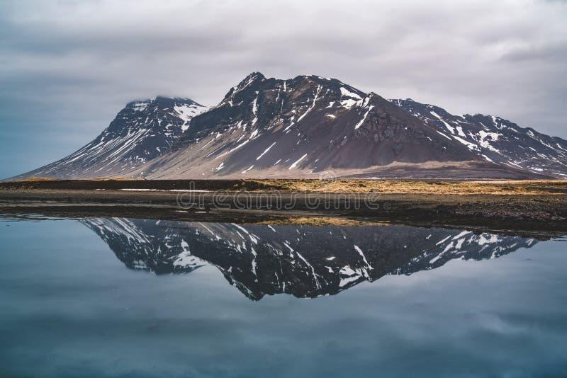 Reflexión de una montaña en Islandia en una bahía de Océano Atlántico del norte imagenes de archivo
