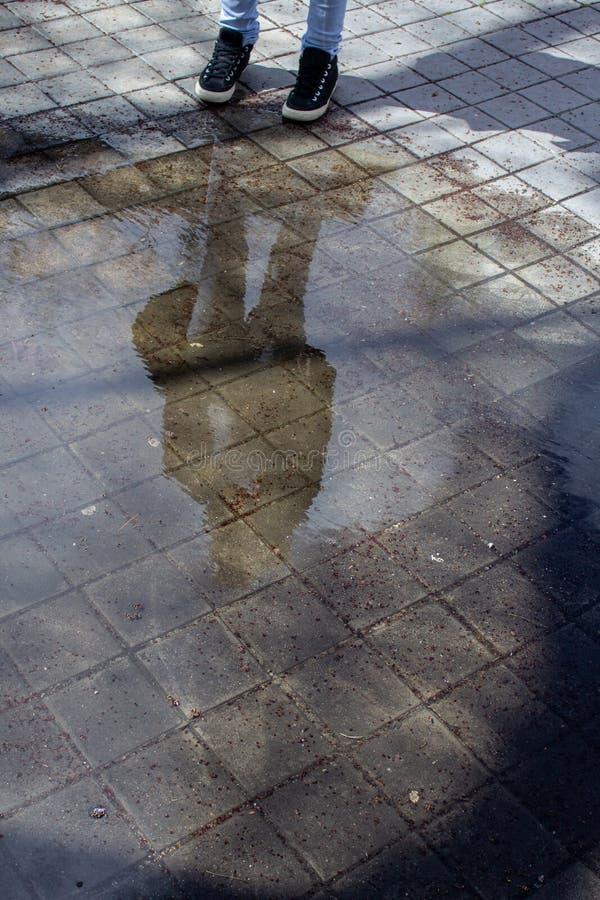 Reflexión de una mujer joven en un charco en la calle fotos de archivo