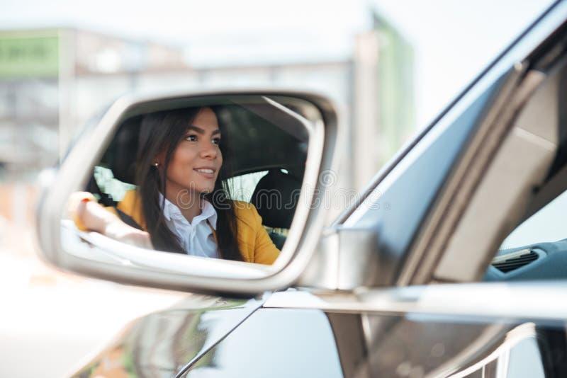 Reflexión de una mujer joven que compra un nuevo coche fotografía de archivo