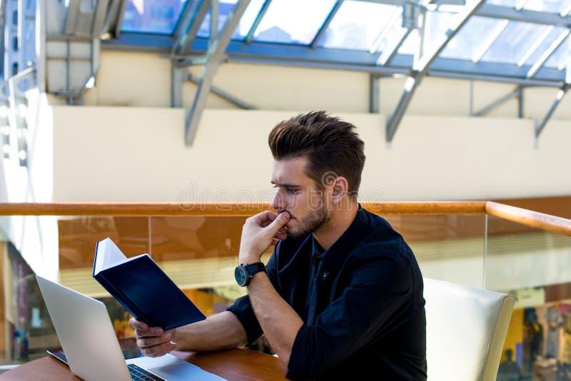 Reflexión del banquero acertado masculino que usa el cuaderno y el netbook, sentándose en empresa fotos de archivo libres de regalías