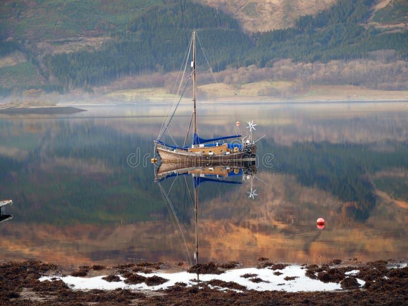 Reflexión del barco de navegación en el lago Linnhe imagenes de archivo