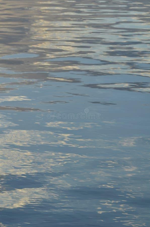Reflexión del cielo azul con las nubes blancas en el agua, fondo abstracto foto de archivo