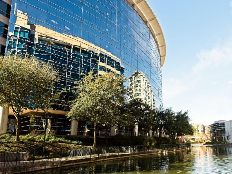Reflexión del edificio a lo largo del canal los arbolados TX fotografía de archivo