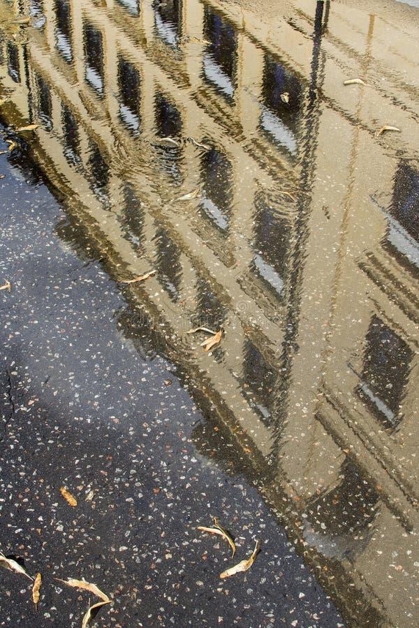 Reflexión del edificio viejo en agua en la calle fotografía de archivo libre de regalías
