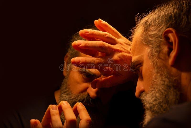 Reflexión del hombre barbudo en una oscuridad, llevando a cabo su cabeza con sus manos con la expresión dolorosa imagen de archivo