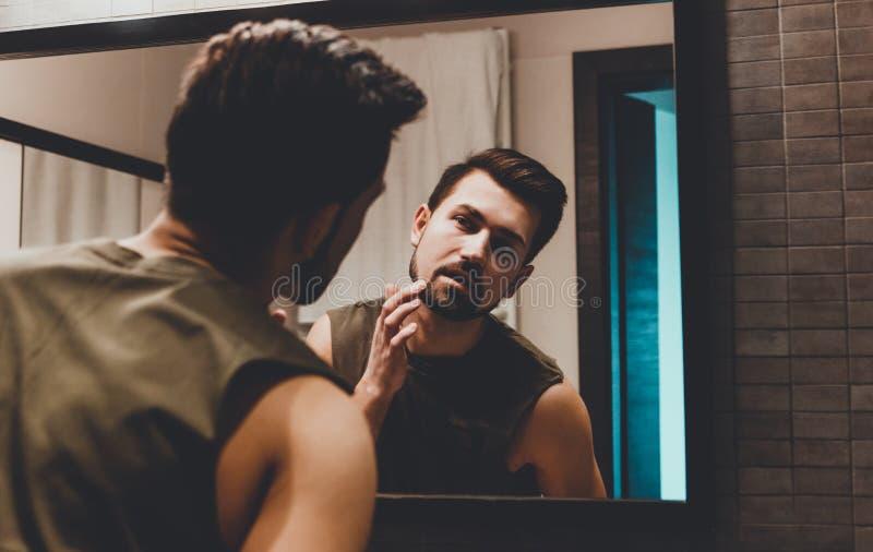 Reflexión del hombre joven en el espejo del cuarto de baño que mira en su cara fotos de archivo