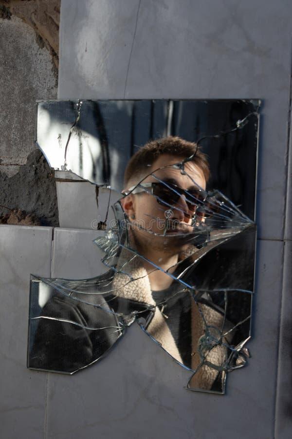 Reflexión del muchacho con las gafas de sol en un espejo quebrado foto de archivo