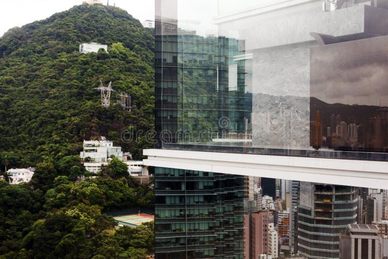 Reflexión del paisaje urbano en un edificio de cristal y del paisaje en la ciudad de Hong Kong, China fotografía de archivo